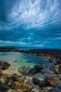 Dusk over ocean volcanic rock pool on a cloudy sky Stock Photo