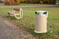 Dust bin bench and autumn leaves somewhere in park Royalty Free Stock Image