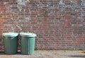 Dustbins trashcan rubbish bins outside against brick wall Royalty Free Stock Photo