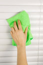 Dusting window blinds vertical photo of female hand cleaning with microfiber cloth Royalty Free Stock Photography