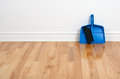 Dustpan and brush on a wooden floor Royalty Free Stock Photo