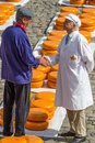 Dutch cheese market in gouda a farmer and a merchant wearing traditional attire agree on the sale of rows of traditional at the Royalty Free Stock Images