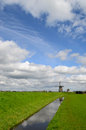 Dutch clouds in the sky over a windmill a meadow a ditch and a dike in holland Stock Image