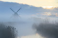 Dutch dawn foggy at a windmill in the countryside Stock Images