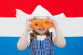 Dutch girl with orange donuts and Netherlands flag