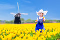 Dutch girl in tulip field in holland adorable curly toddler wearing traditional national costume dress and hat playing a of Stock Photography