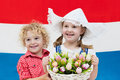 Dutch kids with tulip flowers and Netherlands flag Royalty Free Stock Photo
