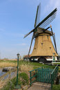 Dutch landscape with a windmill bridge over water and garden path in Royalty Free Stock Photography