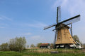 Dutch landscape with a windmill near canal in Royalty Free Stock Photo