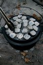 Dutch oven with briquettes and tongs Royalty Free Stock Photo