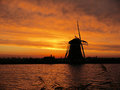 Dutch scenery beautiful red sky clouds water and a windmill this is a typical Stock Photography