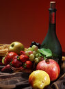 Dutch still life on a tablecloth of juicy fruits and a dusty old bottle of wine on a red background, vertical Royalty Free Stock Photo