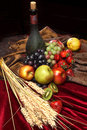 Dutch still life on a velvet tablecloth of juicy fruits, dusty old bottle of wine and ears of wheat, vertical Royalty Free Stock Photo
