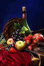 Dutch still life on a velvet tablecloth of juicy fruits and a dusty old bottle of wine, vertical Royalty Free Stock Photo