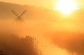 Dutch sunrise windmill during a foggy in the countryside Stock Images