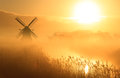 Dutch sunrise windmill during a foggy in the countryside Stock Photo