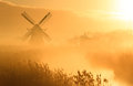 Dutch sunrise windmill during a foggy in the countryside Royalty Free Stock Photography