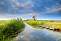 Dutch windmill and blue morning sky reflected in river Stock Photo