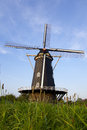 Dutch windmill a with a blue sky behind Royalty Free Stock Photo