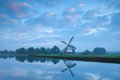 Dutch windmill close to river during calm sunrise pastel holland Royalty Free Stock Images