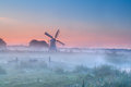 Dutch windmill in dense morning fog at summer sunrise Stock Photography