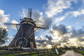 Dutch windmill at and facing the sunset with dramatics clouds and shiny sunset landscape Royalty Free Stock Images