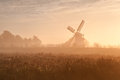 Dutch windmill in fog and morning sunshine Royalty Free Stock Photo