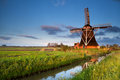 Dutch windmill in morning sunrise sunlight reflected river holland Stock Photos