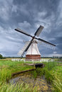 Dutch windmill over clouded sky in summer holland Stock Photo