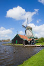 Dutch windmill over river waters zaan holland Stock Photography