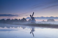 Dutch windmill reflected in river in sunrise fog Royalty Free Stock Photo