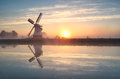 Dutch windmill reflected in river at sunrise groningen netherlands Royalty Free Stock Photo