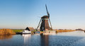 Dutch windmill on the river banks Royalty Free Stock Images