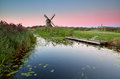 Dutch windmill by river at sunrise with water lily holland Royalty Free Stock Image