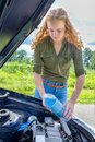 Dutch woman filling car reservoir with fluid in bottle Royalty Free Stock Photo