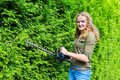 Dutch woman pruning hedge with electric hedge shears Royalty Free Stock Photo