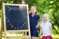 Dwa excited małe siostry chalkboard Zdjęcie Stock