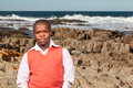 Dwarf model dwarfish african man dressed stylishly posing with the rocky beach in the background Stock Photos