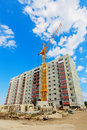 Dwelling house and tower crane on the construction site beneath blue cloudy sky Stock Photo