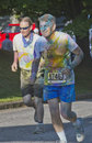 Dye drenched male runners in the asheville color run north carolina usa july two men colorful dyes one with his face masked by Stock Image