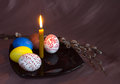 Dyed and painted eggs have on a plate with a candle decorated with sprigs of willow Royalty Free Stock Photography