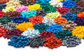 Dyed plastic granulate resins different tinted polymer pellets in marketing office on white table Stock Images