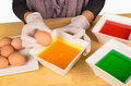 Dyeing easter eggs hands with gloves getting ready to dye Stock Photos