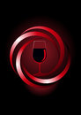 Dynamic icon for red wine with a glass of inside a spiral twirled frame emerging from the shadows on a dark background Royalty Free Stock Photo