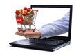 E commerce gift shopping cart full of gold boxes and red sale sign through laptop monitor concept for Stock Photos