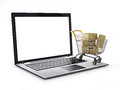 E-commerce. Shopping cart with cardboard boxes on laptop. Royalty Free Stock Photo