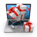 E-commerce. Shopping cart and gifts on laptop Royalty Free Stock Photography