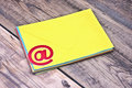 E mail symbol and pile colorful envelopes on old wooden background Royalty Free Stock Photo