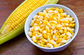 Ear of corn and corn seed in bowl on wood table Royalty Free Stock Photos