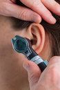 Ear examining with an otoscope close up Stock Image